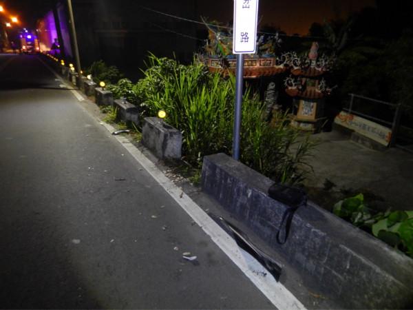 警方在路旁水泥護欄發現機車零件散落。(記者張軒哲翻攝)