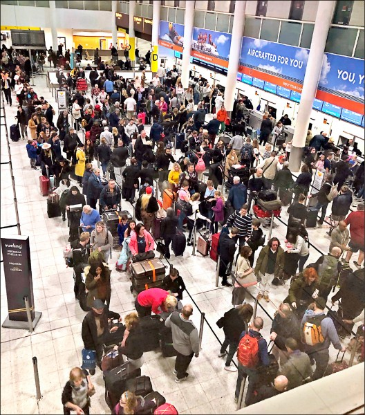 倫敦蓋特威克機場十九日受到兩架無人機干擾,導致所有航班全面暫停起降,受到影響的旅客二十日在機場滯留,或在服務台前大排長龍。(美聯社)