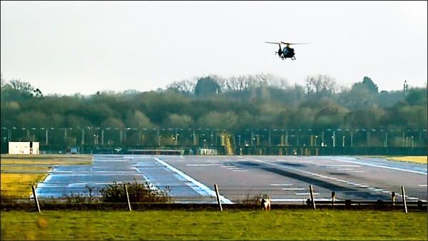 英國警方出動直升機在機場巡視,追查無人機及其操作者的下落。(美聯社)