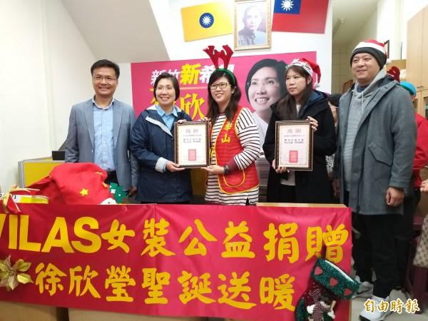 徐欣瑩搭起結合社會資源的橋梁,讓需要得到幫助的人與想要投入社會公益的品牌公司,都能夠達成目的。受贈單位代表致贈感謝狀。(記者廖雪茹攝)