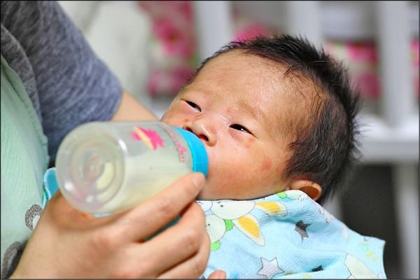 英國牛津大學學者指出,全球生育率下降值得慶賀,而非視為警訊。圖為南韓首爾一名社工在社區教堂餵食嬰兒。(法新社檔案照)