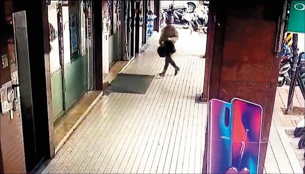 穿著米色大衣、頭戴銀色安全帽搶匪,持槍、提黑色袋子衝進板橋陽信銀行溪洲分行行搶。(記者吳仁捷翻攝)