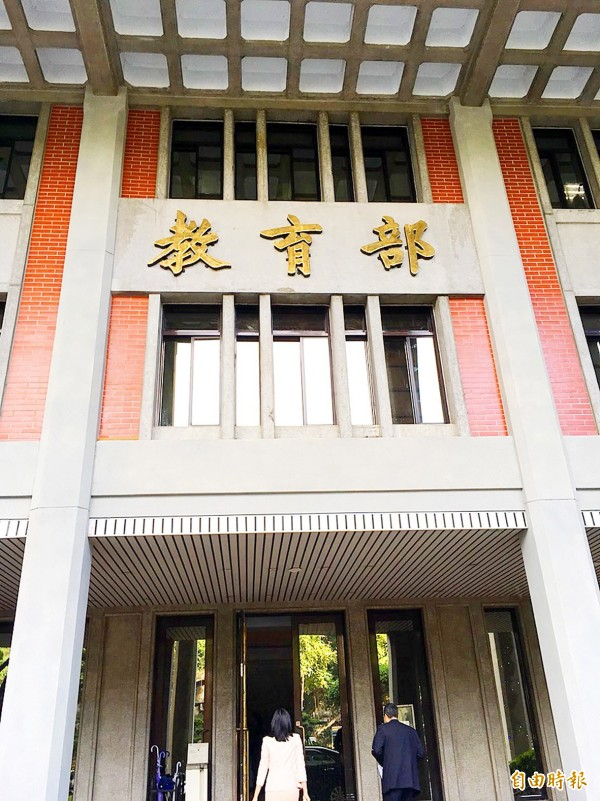 Two people walk through the main entrance of the Ministry of Education in Taipei on Friday. Photo: Lin Hsiao-yun, Taipei Times