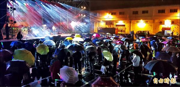 基隆市跨年晚會昨晚登場,基隆港西岸碼頭有不少粉絲撐傘、穿雨衣,冒雨聆聽獨立樂團演出。(記者俞肇福攝)