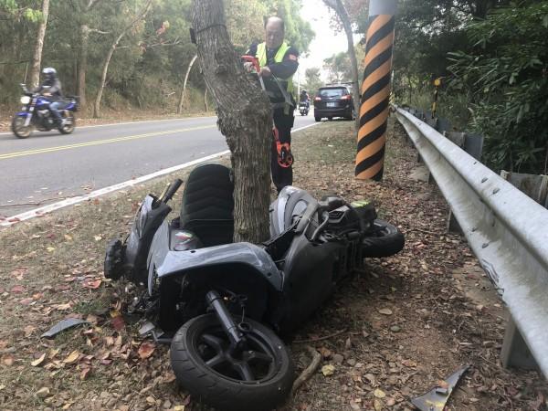 機車衝撞護欄後再反彈撞擊路樹,不偏不倚的「卡」在樹幹裡,員警直呼:「離奇!」(記者湯世名翻攝)
