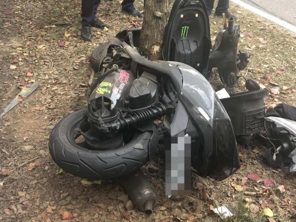 機車衝撞護欄後再反彈撞擊路樹,正好「卡」在樹幹裡,機車嚴重毀損。(記者湯世名翻攝)