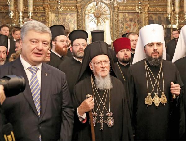 君士坦丁堡牧首巴爾多祿茂一世(中),五日在土耳其伊斯坦堡聖喬治主教座堂簽名認可烏克蘭正教會的自主教會地位,烏克蘭總統波洛申科(左)與烏克蘭正教會領袖基輔都主教葉皮凡尼(右)皆出席見證。圖為三人在簽署儀式後離開現場。(歐新社)