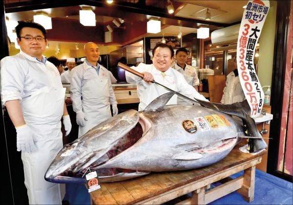 圖為木村(中)以天價買下黑鮪魚後拿著長刀作勢要表演解剖秀。(法新社)
