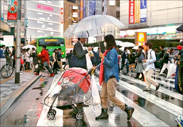 2017年10月29日雨天的東京,一名戴口罩的媽媽正撐傘推著嬰兒手推車過馬路。(歐新社檔案照)