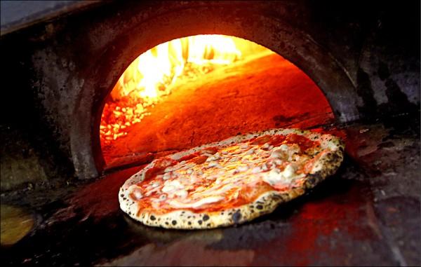義大利學者研究「完美披薩方程式」,指出烘烤瑪格麗特披薩時,用攝氏330度的磚窯烘製2分鐘,相當於用攝氏230度的電烤箱烘製170秒。(路透檔案照)