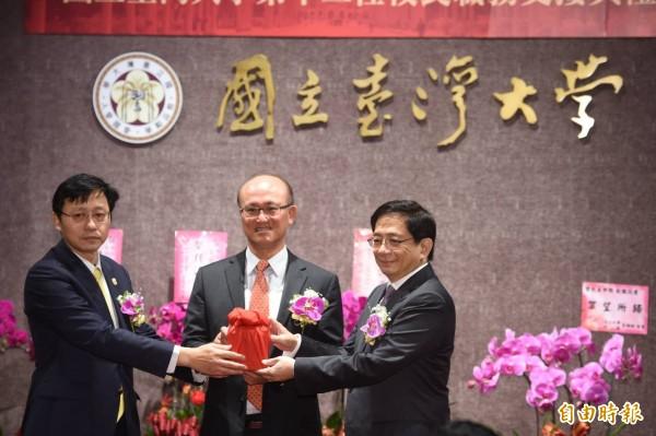 台灣大學今舉辦第12屆校長交接上任典禮,管中閔(右)正式接下印信成為台大校長。(記者劉信德攝)