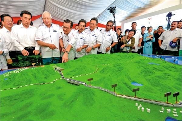 大馬財政部長林冠英將調查東海岸銜接鐵路一案。圖為2017年8月前首相納吉(左3)視察模型圖。(美聯社檔案照)