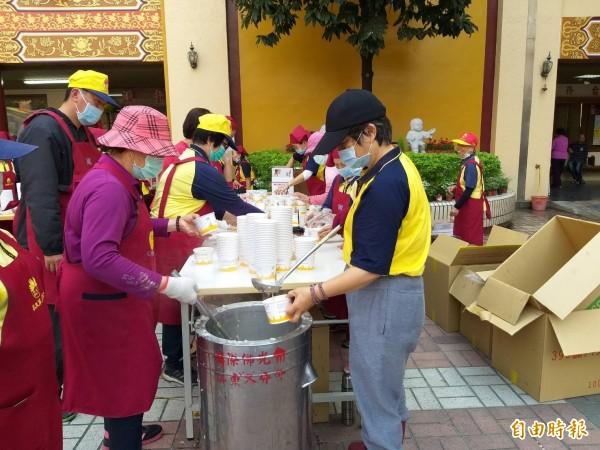 志工們忙著製作臘八粥。(記者葉永騫攝)