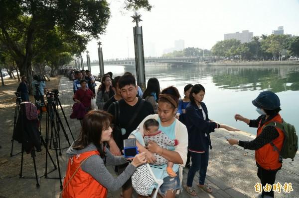 年輕媽媽背著孩子領牌。(記者張忠義攝)