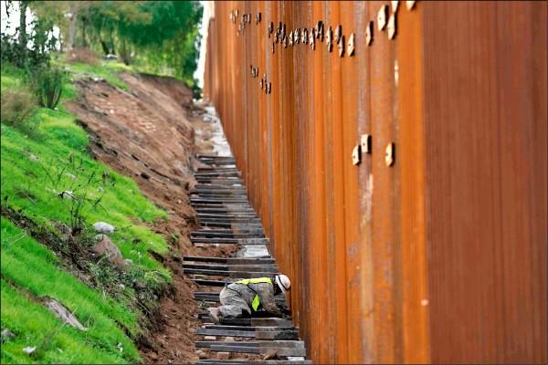 圖是工作人員九日在美墨邊境整理圍籬。(法新社)