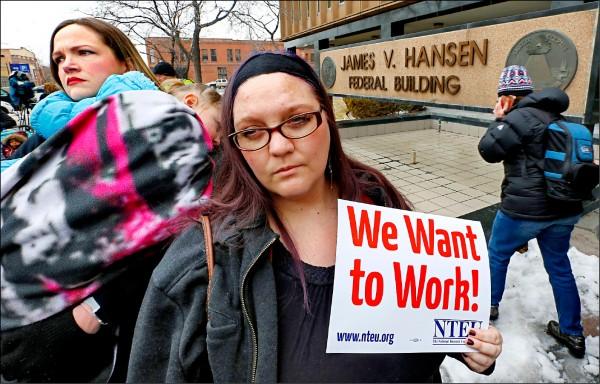 在猶他州奧格登市聯邦大樓外,國稅局員工舉著「我們要工作」的字牌抗議。(美聯社)