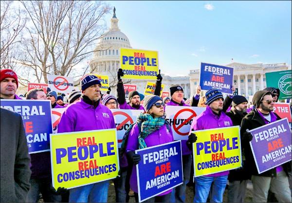美國聯邦政府被迫放無薪假的員工,10日於國會山莊外舉著寫有「聯邦工人是美國工人」等字樣的抗議標語,要求終結政府關門。 (美聯社)