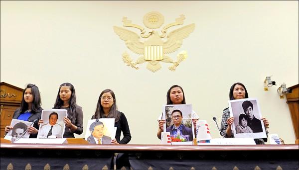 圖為王天安(左三)二○一三年十二月拿著王炳章照片,出席美國聯邦眾議院外交委員會聽證會。(美聯社檔案照)