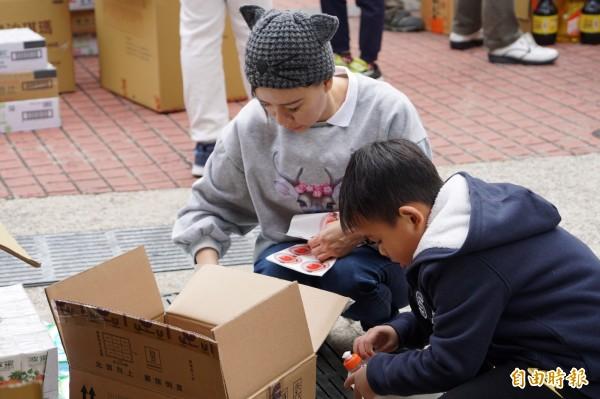 不少家長帶著小朋友到場協助分裝物資,獻愛心。(記者張勳騰攝)