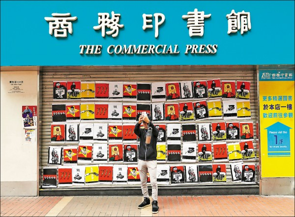 香港三大書局「三中商」屢被投訴涉及「政治審查」。圖為去年十一月四日,香港商務印書館門前被人貼上中國異議漫畫家「巴丟草」(Badiucao)大批作品,抗議他因遭恐嚇而不得不取消在香港的展覽。(美聯社檔案照)