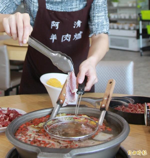 老闆娘葉致薰示範「涮羊肉」吃法,里肌肉放入羊肉鍋湯底裡涮五秒,略呈粉紅色肉片,入口即化。(記者陳冠備攝)