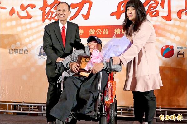 經銷商黃國財(中),獲頒「永不放棄獎」,由台彩董事長薛香川(左)頒贈獎牌,黃國財女兒(右)獻花祝賀。 (記者吳佳蓉攝)