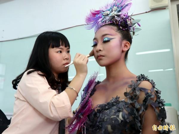 三民家商美容科二年級學生郭玲瓏(左)表演得獎作品「孔雀」。(記者黃旭磊攝)