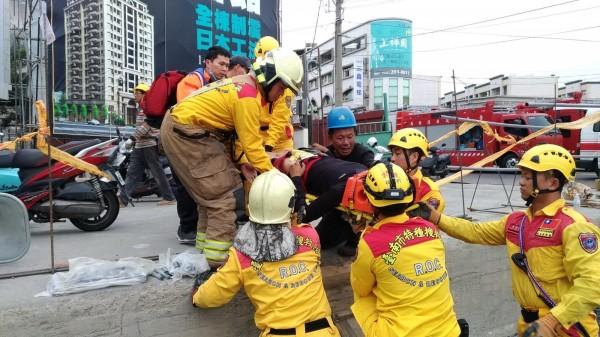 消防隊員協助遭鋼筋砸傷的工人脫困,將他緊急送醫。(記者吳俊鋒翻攝)