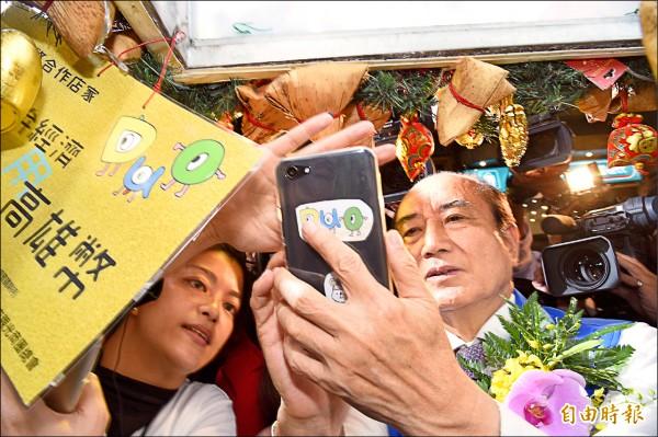 高雄市推出高雄幣行動支付APP,昨請來前立法院長王金平,在六合夜市進行宣傳並親自體驗。(記者張忠義攝)