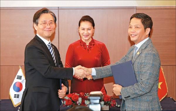2018年12月6日在首爾一家飯店,與訪韓的越南工商部長陳俊英(右)於簽署一份達1000億美元的韓、越雙邊貿易行動計畫後,欣然握手。中間觀禮的則是越南國會主席阮氏金銀。(歐新社檔案照)