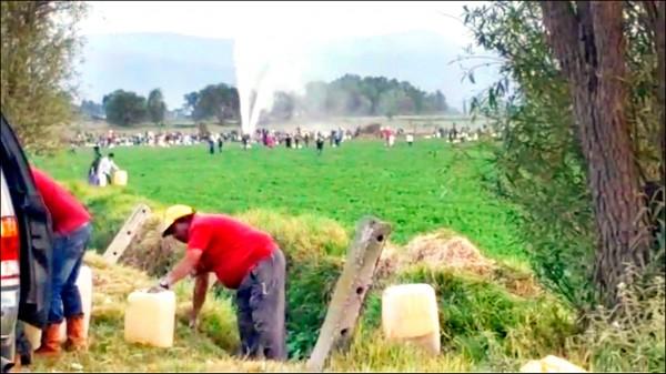 18日爆炸發生時,許多居民正拿油罐與水桶偷接自破裂油管噴湧而出的汽油。(路透)