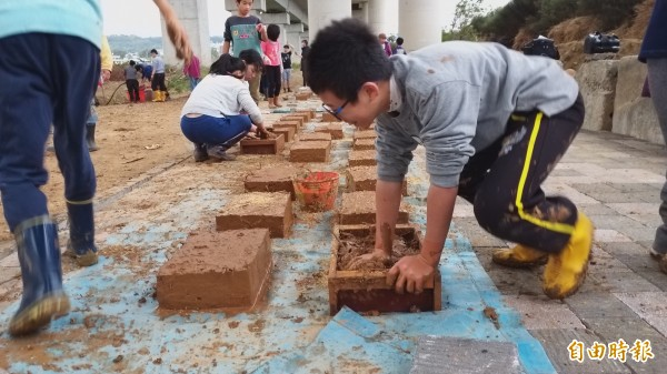 新竹縣青少年社規師成長營一群國小學童,今起6天由傳統泥水師傅帶領,捲起袖子一起認識傳統工法、學習動手做泥磚。(記者廖雪茹攝)