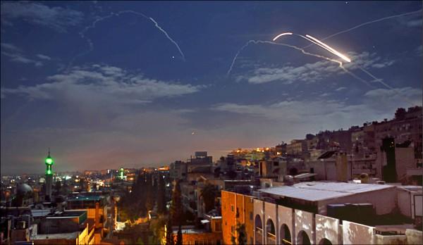 以色列二十一日出動戰機和飛彈空襲敘利亞境內的伊朗軍事目標,報復伊朗武裝部隊二十日對戈蘭高地的攻擊。圖為以國飛彈與敘國防空飛彈劃過敘國首都大馬士革上空,展開「矛盾對決」。(法新社)
