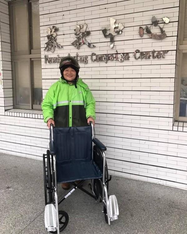 陳姓婦人昨雨衣、安全帽未脫,就急著將新購的輪椅推進聖母醫院募款中心。(聖母醫院提供)