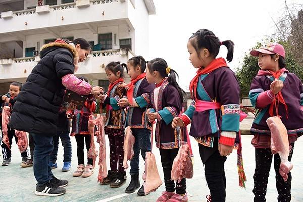 廣西一所偏鄉小學以「豬肉」當作獎品,發給71名學期表現優良的學生。(圖擷取自澎湃新聞)