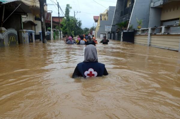 一名志工在洪水中跋涉。(路透)