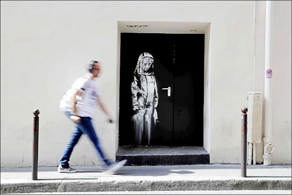班克西在巴黎巴塔克蘭劇場 逃生門上繪製的一幅壁畫被偷走。(法新社檔案照)