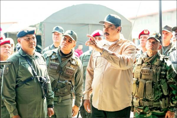 委內瑞拉總統馬杜羅(中)為展現獲軍方力挺,廿七日在首都卡拉卡斯檢閱軍事演習。(歐新社)