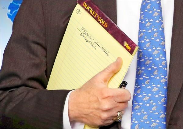 波頓手上的筆記本,被媒體拍到寫有「五千名部隊到哥倫比亞」字句。(路透)