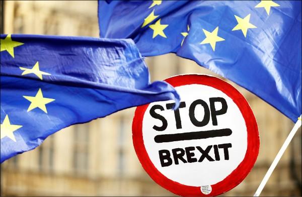 英國下議院廿九日表決多項脫歐協議修正案之前,反對脫歐的民眾在倫敦街頭揮舞歐盟旗幟表達抗議。(美聯社)