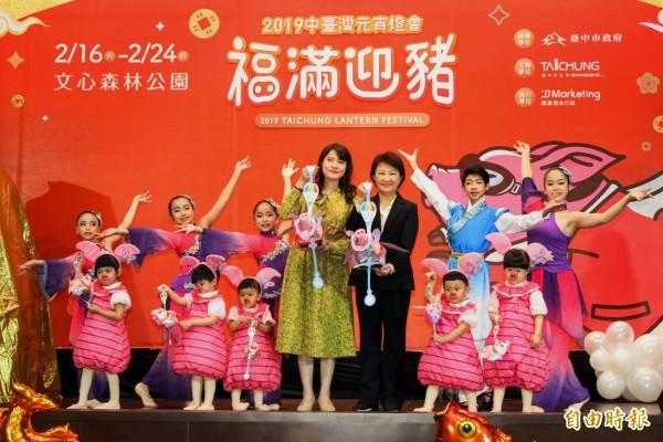 台中市長盧秀燕(前排右3)、觀旅局長林筱淇(前排右4)與小朋友提著「飛天豬」小提燈,邀請民眾參觀中台灣元宵燈會。(記者張菁雅攝)