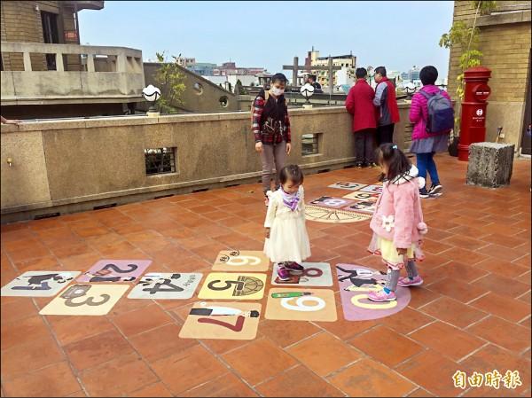 林百貨頂樓地板設計跳格子,吸引小朋友互動。(記者劉婉君攝)