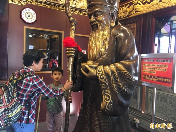 參拜完南山福德宮後,以順時針方向摸3圈土地公銅像手中的元寶,吸收滿滿的財運。(記者何玉華攝)