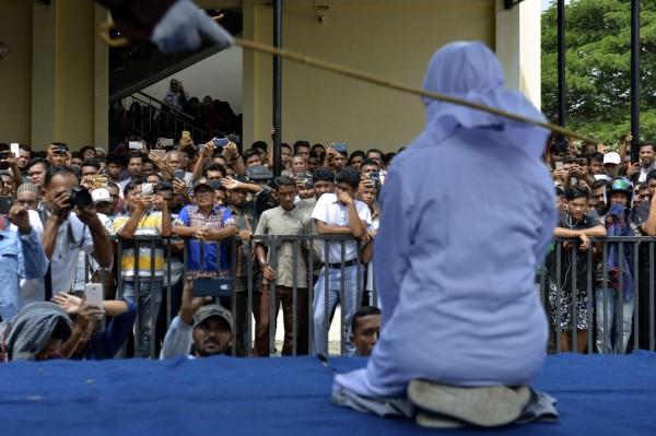 週四,亞齊首府班達亞齊的清真寺外,有數百位民眾觀看18歲女大生和她的男友被公開鞭刑。(法新社)
