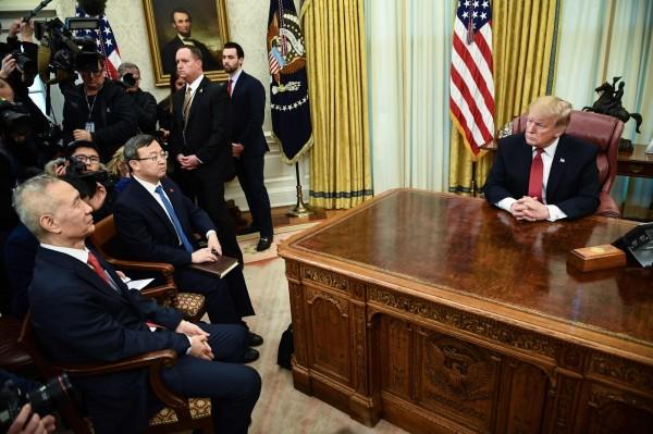 川普坐在辦公桌後與劉鶴(左)談話。(法新社)