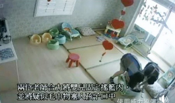 網友指出,老師將嬰兒固定在搖籃中,並疑似將毛巾塞入其口中。(記者張菁雅翻攝)