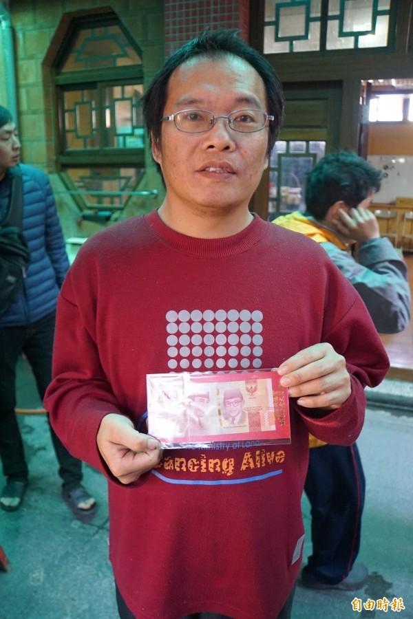 信眾拿到「10萬」 印尼盾紅包,覺得相當幸運。(記者詹士弘攝)