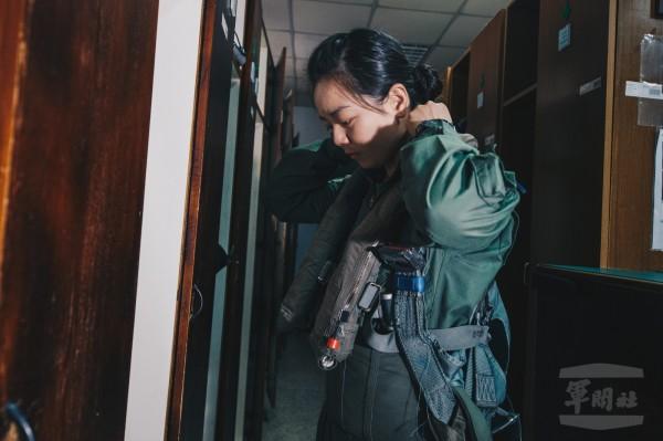 中尉郭文靜在個裝室穿戴個人裝備,包含抗G衣,適身套袋以及救生背心。(圖:軍聞社提供)