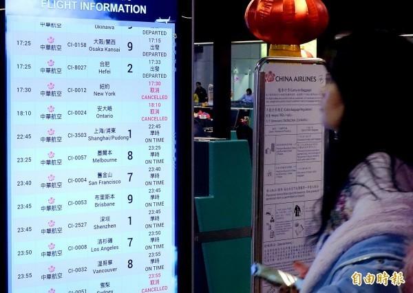 華航機師持續罷工,華航陸續公布取消航班,圖為旅客在桃園機場查詢航班資訊。(記者朱沛雄攝)