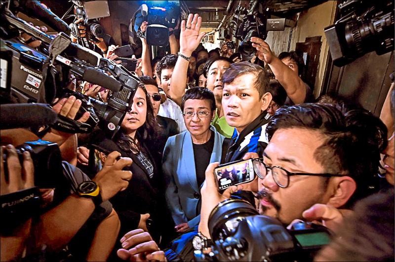 菲律賓網路新聞平台「Rappler」執行主編瑞薩(Maria Ressa,圖中戴眼鏡者),十三日以涉嫌網路誹謗案被捕。圖為她十四日獲保釋後,在馬尼拉地方法院外,被媒體記者團團圍住,爭相採訪報導。(歐新社)